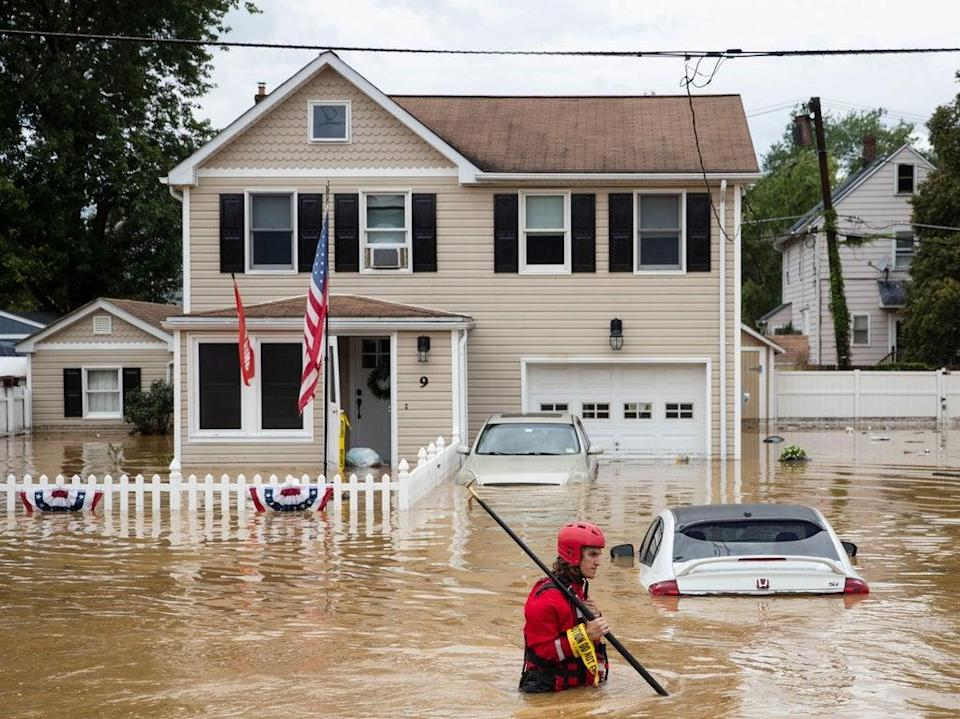 A New Market Volunteer Fire Company rescue crew member wades through high waters following a flash flood, as Tropical Storm Henri makes landfall, in Helmetta, New Jersey (AFP via Getty Images)
