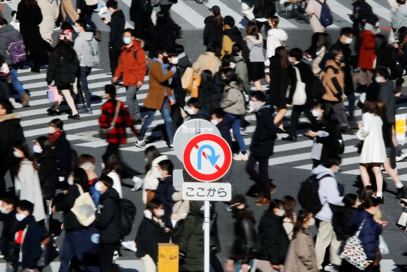 Passersby wearing protective face masks walks at Shibuya crossing amid coronavirus disease (COVID-19) outbreak in Tokyo