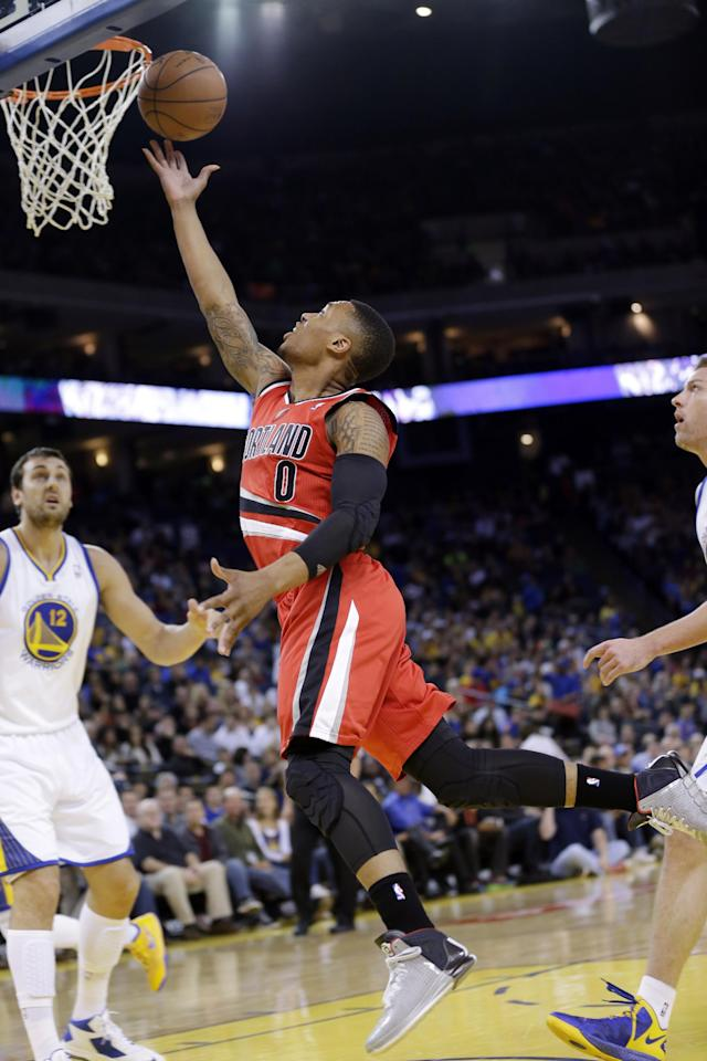 Portland Trail Blazers' Damian Lillard (0) goes up for a layup past Golden State Warriors' Andrew Bogut (12) during the first half of an NBA basketball game on Sunday, Jan. 26, 2014, in Oakland, Calif. (AP Photo/Marcio Jose Sanchez)
