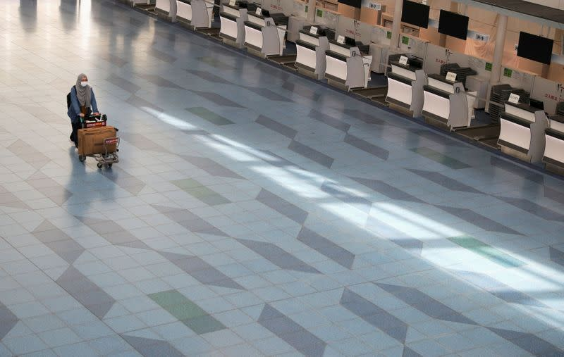 FILE PHOTO: A woman pushes a luggage cart near closed check-in counters at Haneda Airport in Tokyo