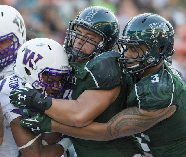 Washington running back Dwayne Washington, left, is stacked up by Hawaii defensive lineman Beau Yap, center, and linebacker TJ Taimatuia (3) in the third quarter of an NCAA college football game, Saturday, Aug. 30, 2014, in Honolulu. (AP Photo/Eugene Tanner)