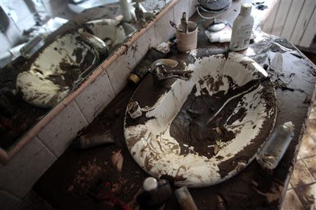 A sink is seen covered in mud in a bathroom of a house following extreme rainfall in Olbia on Sardinia island November 20, 2013. REUTERS/Tony Gentile
