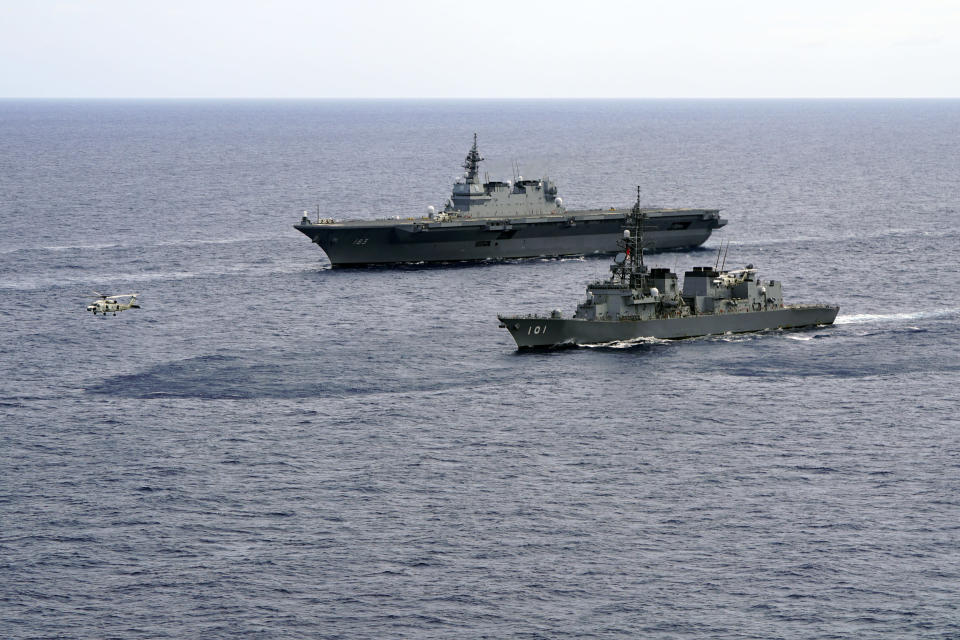 FILE - In this June 28, 2019, file photo, Japan's Maritime Self-Defense Force helicopter carrier Izumo (DDH-183) and destroyer JS Murasame (DD-101) participate in drills that included maritime navigation and emergency response exercises in Sulu Sea. Japan approved Friday, Dec. 20, 2019, a draft defense budget that included cost to develop own fighter jets to succeed the nation's aging warplanes and import some of F-35 stealth fighters as components for assembly at home rather than importing the expensive American warplanes as finished products to reduce costs and acquire expertise. To accommodate the F-35Bs, the Defense Ministry will spend 3.1 billion yen ($290 million) to reconfigure one of its two helicopter carriers, Izumo, with a heat-resistant flight deck and guiding lights, beginning next year. (AP Photo/Emily Wang, File)
