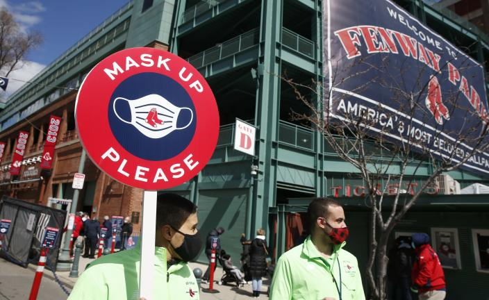 Members of the Boston Red Sox health compliance crew stand at the entrance to Fenway Park before an opening day baseball game between the Red Sox and the Baltimore Orioles, Friday, April 2, 2021, in Boston. (AP Photo/Michael Dwyer)