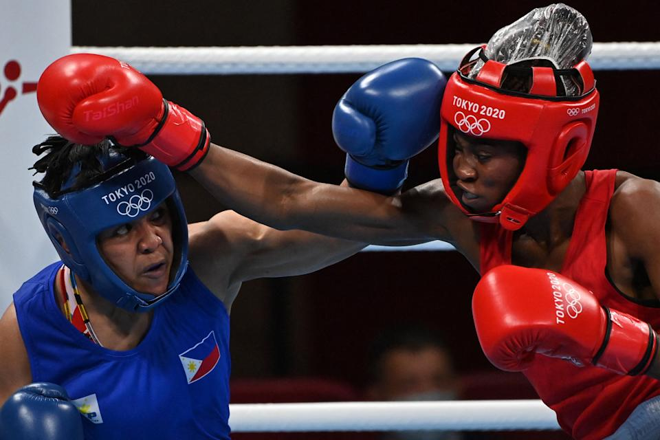 DR Congo's Marcelat Sakobi Matshu (red) and Philippines' Nesthy Petecio fight during their women's feather (54-57kg) preliminaries boxing match during the Tokyo 2020 Olympic Games at the Kokugikan Arena in Tokyo on July 24, 2021. (Photo by Luis ROBAYO / AFP) (Photo by LUIS ROBAYO/AFP via Getty Images)