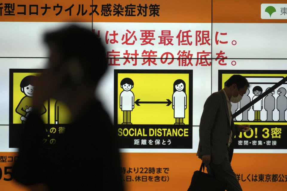 People walk past a public awareness sign for social distancing to help reduce the spread of the coronavirus Tuesday, June 22, 2021, in Tokyo. The Japanese capital confirmed more than 430 new coronavirus cases on Tuesday. (AP Photo/Eugene Hoshiko)