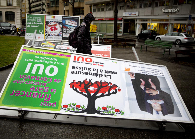 "A man passes by election posters demanding a stop for immigration to Switzerland in the center of Geneva, Switzerland, Monday, Feb. 10, 2014. The placard in the center foreground reads ' excess harms Switzerland'. The choice by Swiss voters to reimpose curbs on immigration is sending shockwaves throughout the European Union, with EU leaders on Monday warning the Swiss had violated the ""sacred principle"" of Europeans' freedom of movement and politicians anxiously trying to gauge the vote's impact on burgeoning anti-foreigner movements in other countries. (AP Photo/Anja Niedringhaus)"