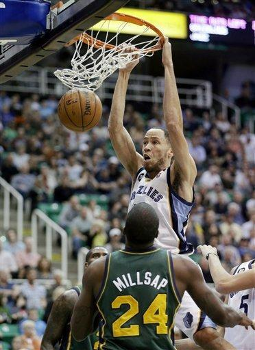 Utah Jazz's Paul Millsap (24) watches as Memphis Grizzlies' Tayshaun Prince, rear, dunks the ball in the second quarter during an NBA basketball game Saturday, March 16, 2013, in Salt Lake City. (AP Photo/Rick Bowmer)