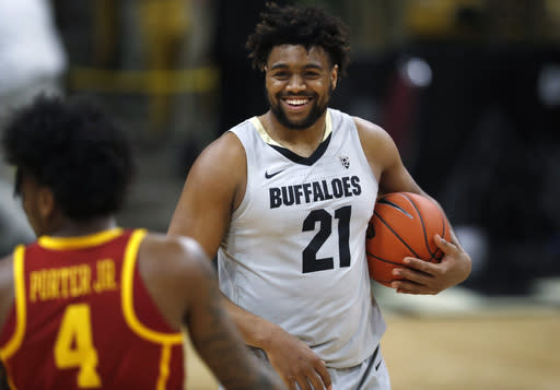 Colorado forward Evan Battey, back, smiles as he holds the ball as time runs out in the second half of an NCAA college basketball game as USC guard Kevin Porter Jr. heads off the court Saturday, March 9, 2019, in Boulder, Colo. Colorado won 78-67. (AP Photo/David Zalubowski)