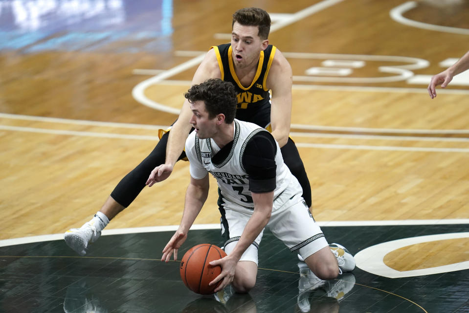 Iowa guard Jordan Bohannon (3) defends Michigan State guard Foster Loyer (3) in the first half of an NCAA college basketball game in East Lansing, Mich., Saturday, Feb. 13, 2021. (AP Photo/Paul Sancya)