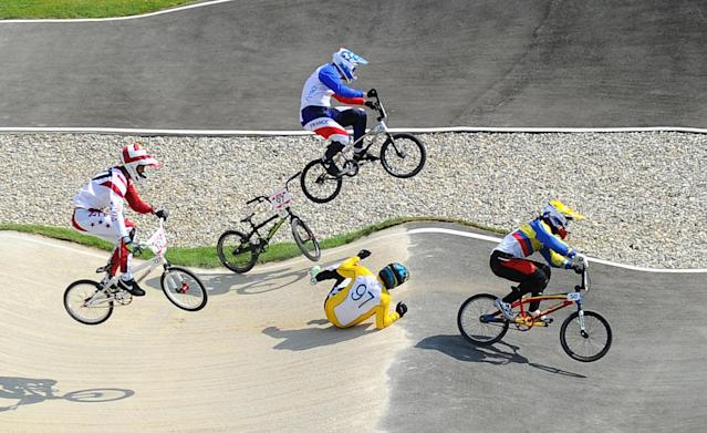 Aug 9, 2012; London, United Kingdom; Khalen Young (AUS), #97 falls off his bike as he attempts to avoid a collision with Ea Buchely Falla (ECU), #50, and Quentin Caleyron (FRA), #14, during the men's BMX quarterfinal run in the London 2012 Olympic Games at BMX Track. Mandatory Credit: James lang-USA TODAY Sports