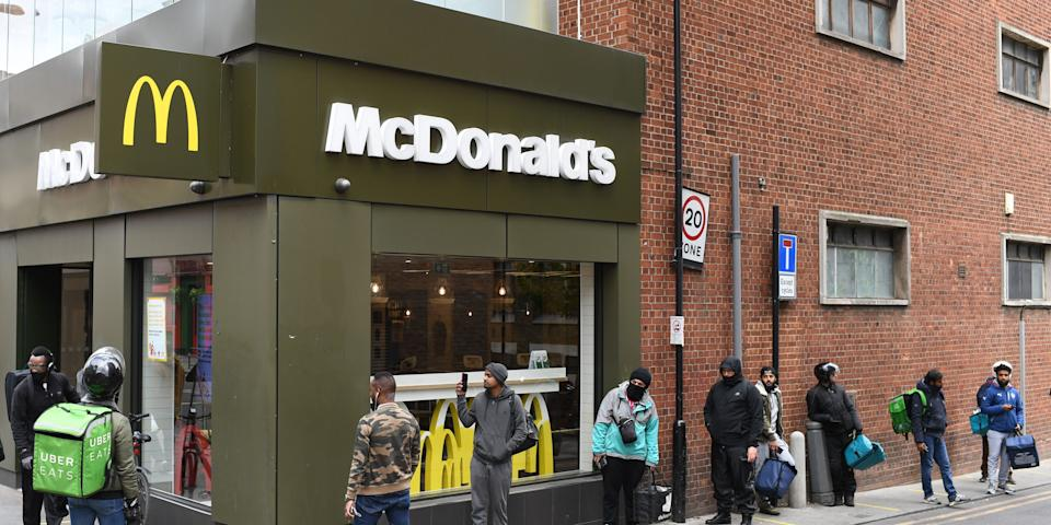 Delivery riders queue up outside a McDonald's restaurant in east London on May 13, 2020.