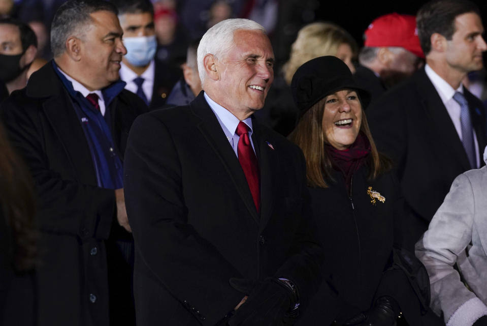 Vice President Mike Pence and his wife Karen listen as President Donald Trump speaks during a campaign rally at Gerald R. Ford International Airport, early Tuesday, Nov. 3, 2020, in Grand Rapids, Mich. (AP Photo/Evan Vucci)
