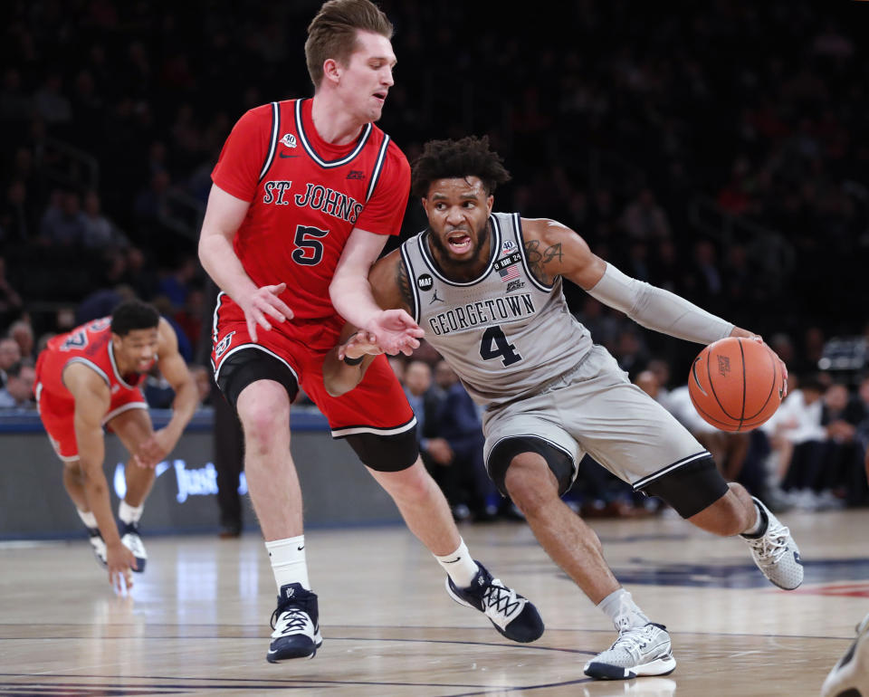 Georgetown guard Jagan Mosely (4) drives around St. John's guard Greg Williams Jr. (4) during the first half of an NCAA college basketball game in the first round of the Big East men's tournament Wednesday, March 11, 2020, in New York. (AP Photo/Kathy Willens)