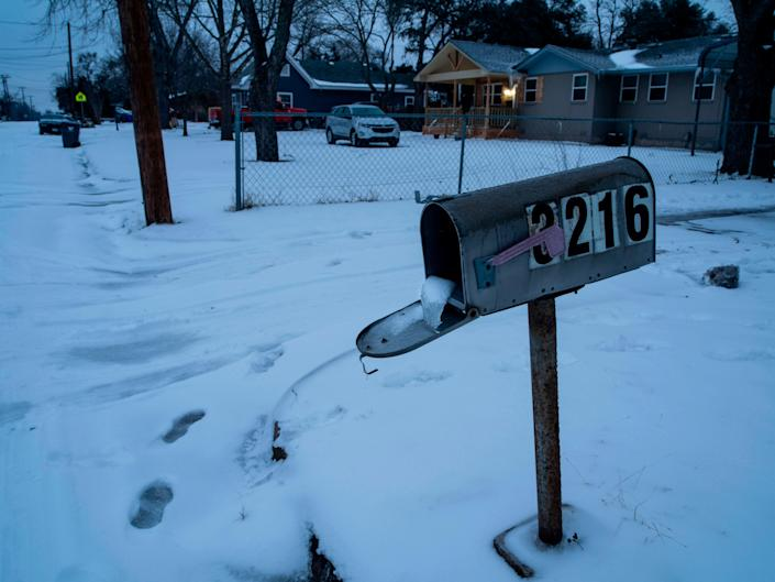 File: A mailbox is seen frozen in a snow-covered neighbourhood in Waco, Texas as severe winter weather conditions over the last few days has forced road closures and power outages over the state on 17 February 2021 (AFP via Getty Images)