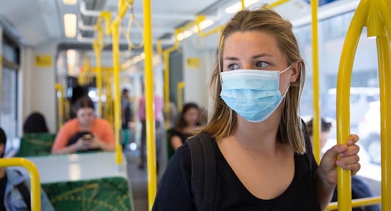 A woman wears a face mask on a tram. Source: Getty