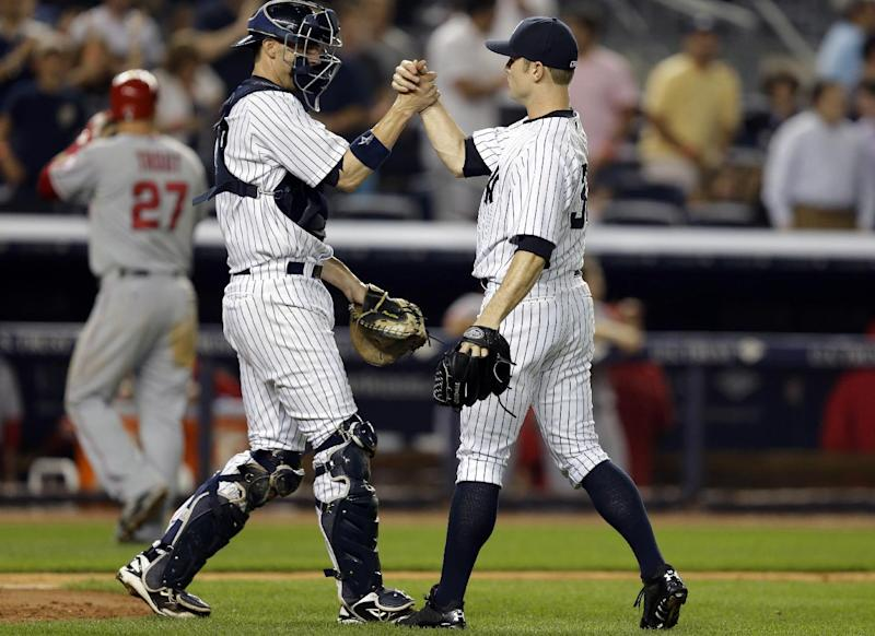 Los Angeles Angels' Mike Trout, far right, heads to the dugout as New York Yankees catcher Chris Stewart (19) congratulates relief pitcher David Robertson (30) who closed out the Yankees 2-1 victory in their baseball game, Monday, Aug. 12, 2013, in New York. (AP Photo/Kathy Willens)