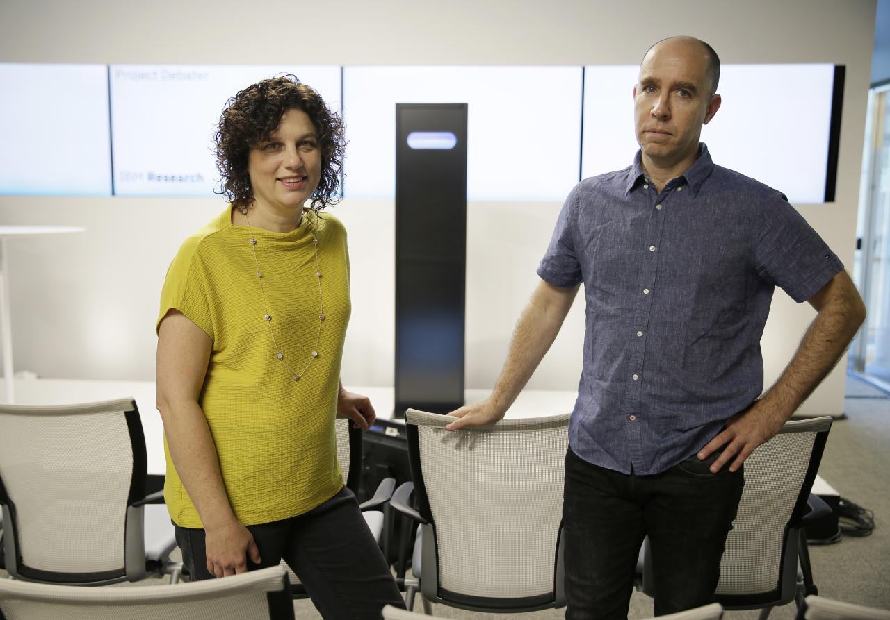 Dr. Ranit Aharonov, manager, left, and Dr. Noam Slonim, right, principal investigator, right, pose for a photo in front of the IBM Project Debater before a debate between the computer and two human debaters Monday, June 18, 2018, in San Francisco. IBM on Monday will pit a computer against two human debaters in the first public demonstration of artificial intelligence technology it's been working on for more than five years. The system, called Project Debater, is designed to be able to listen to an argument, then respond in a natural-sounding way, after pulling in evidence it collects from Wikipedia, journals, newspapers and other sources to make its point. (AP Photo/Eric Risberg)