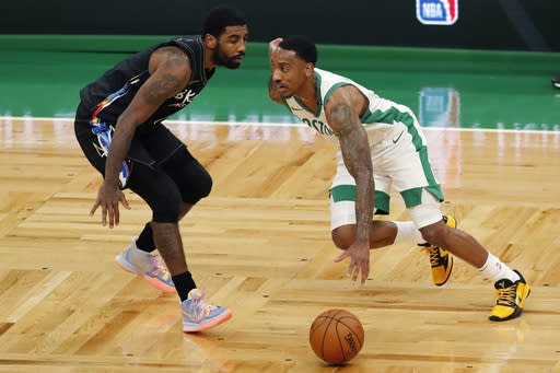 Boston Celtics' Jeff Teague, right, drives past Brooklyn Nets' Kyrie Irving during the first half of an NBA basketball game, Friday, Dec. 25, 2020, in Boston. (AP Photo/Michael Dwyer)