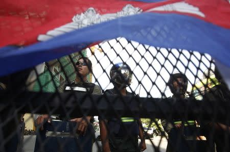 Police officers block a street as protesters demand the release of five opposition members of parliament, near the Phnom Penh Municipal Court