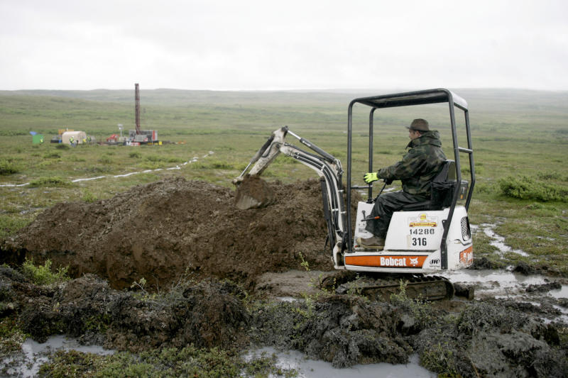 FILE - In this July 13, 2007 file photo, a worker with the Pebble Mine project digs in the Bristol Bay region of Alaska near the village of Iliamma, Alaska. The Trump administration settled a lawsuit Friday, May 12, 2017, over the proposed development of a massive copper and gold deposit near the headwaters of a world-premier salmon fishery in southwest Alaska. (AP Photo/Al Grillo,File)