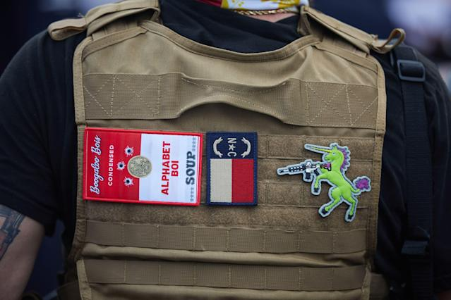 A member of the far-right militia Boogaloo Bois walks next to protesters demonstrating in Charlotte, N.C., on May 29. (Logan Cyrus/AFP via Getty Images)