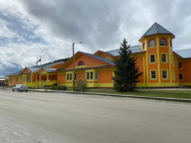 The Robert Service School in Dawson City has received a new paint job. The vibrant look is inspired by Yukon artist Ted Harrison's painted rendition of the school (Chris MacIntyre/CBC - image credit)