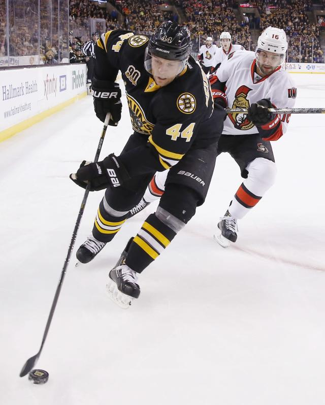 Boston Bruins' Dennis Seidenberg (44) handles the puck in front of Ottawa Senators' Clarke MacArthur (16) in the first period of an NHL hockey game in Boston, Friday, Dec. 27, 2013. (AP Photo/Michael Dwyer)