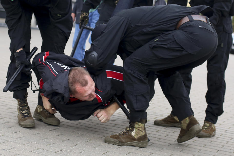 Police detain a demonstrator during an opposition rally to protest the official presidential election results in Minsk, Belarus, Sunday, Sept. 27, 2020. Hundreds of thousands of Belarusians have been protesting daily since the Aug. 9 presidential election. (AP Photo/TUT.by)