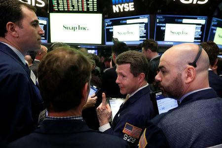 Traders laugh as they work on the floor of the New York Stock Exchange (NYSE) while waiting for Snap Inc. will post their IPO in New York