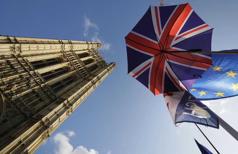 Flags and an umbrella are tied to raiings opposite Britain's parliament buildings in London, Tuesday, Oct. 22, 2019. British lawmakers from across the political spectrum were plotting Tuesday to put the brakes on Prime Minister Boris Johnson's drive to push his European Union divorce bill through the House of Commons in just three days, potentially scuttling the government's hopes of delivering Brexit by Oct. 31. (AP Photo/Kirsty Wigglesworth)