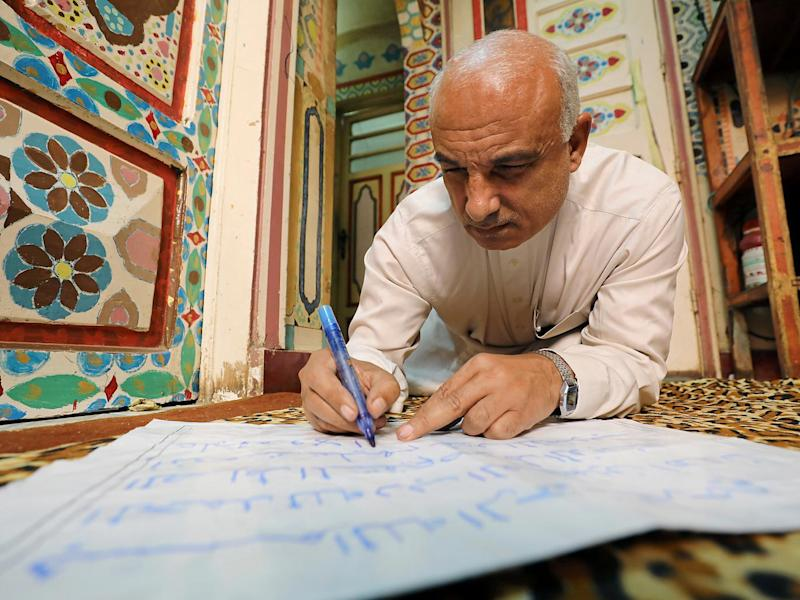 Saad Mohammed writes as he sits on the floor of his studio (Reuters)