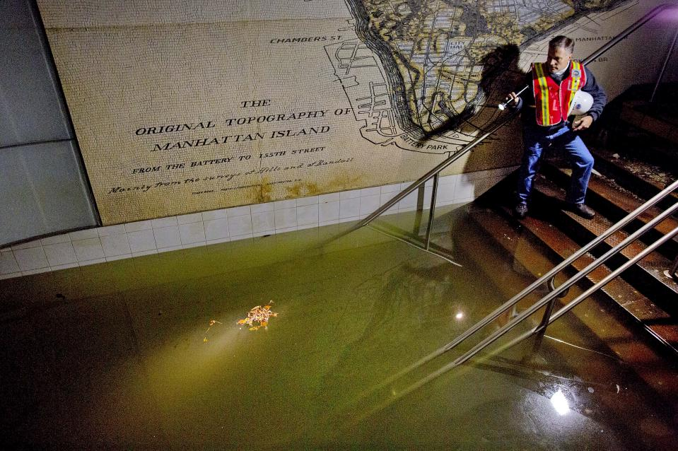 FILE - In this Oct. 31, 2012 file photo, Joseph Leader, Metropolitan Transportation Authority vice president and chief maintenance officer, shines a flashlight on standing water inside the South Ferry #1 subway train station in New York in the wake of Superstorm Sandy. New York's Metropolitan Transportation Authority, which serves several million riders daily on subways, trains and buses, had to repair damage to more than a dozen bridges and tunnels, many pre-dating World War II, caused by tens of millions of gallons of saltwater. (AP Photo/Craig Ruttle, File)