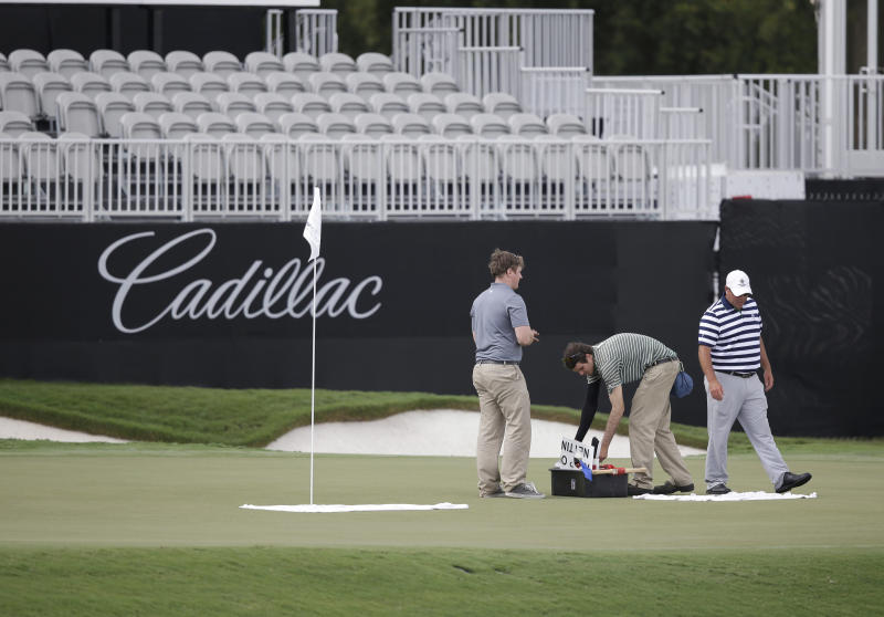 Course workers tend to the 18th hole of the newly redesigned Blue Monster, site of this week's Cadillac Championship golf tournament, Wednesday, March 5, 2014, in Doral, Fla. (AP Photo/Wilfredo Lee)