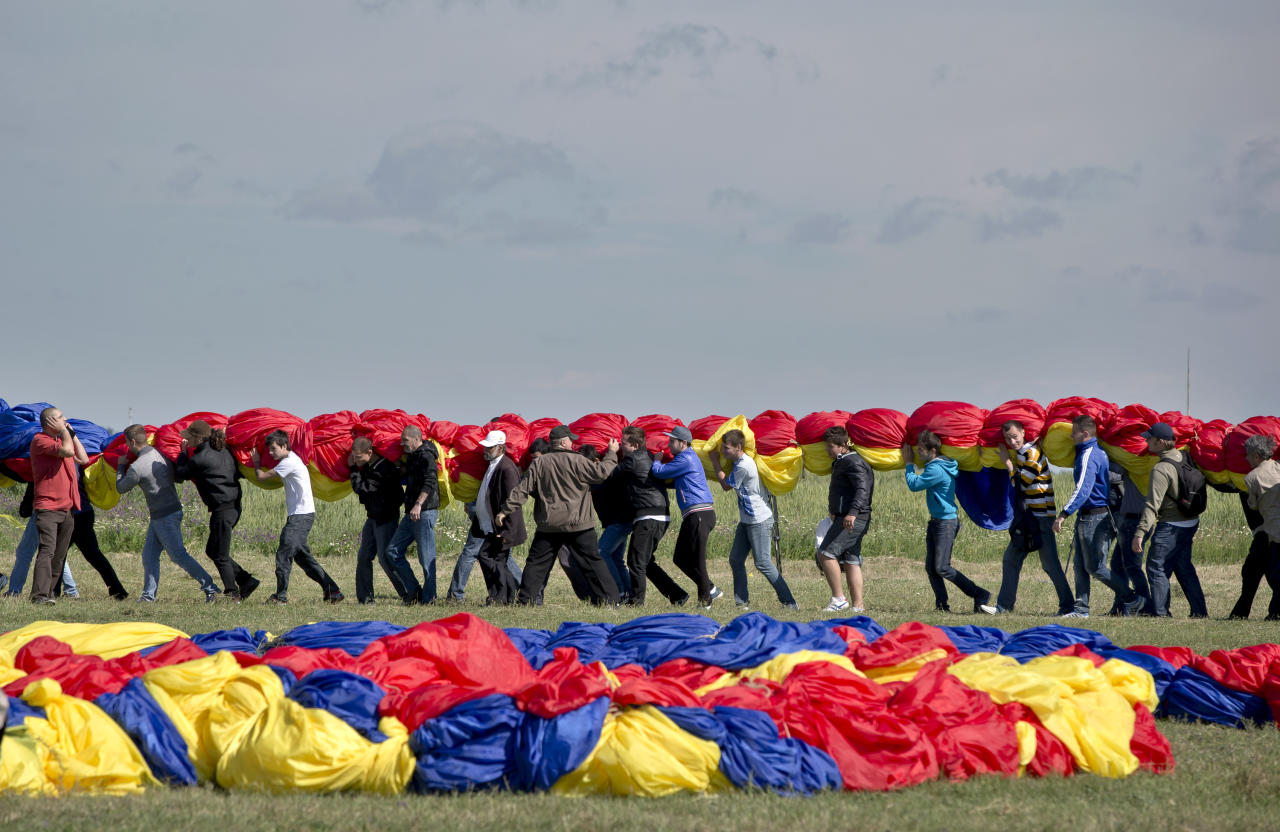 Romanians carry a huge national flag on the Clinceni Airfield, south of Bucharest, Romania, Monday, May 27, 2013. Romania entered the Guinness Book of records after it unveiled the largest flag ever made. It took about 200 people several hours Monday to roll out the five-ton flag of Romania, which organizers said measured 349.4 meters by 226.9 meters, about three times the size of a football pitch.(AP Photo/Vadim Ghirda)