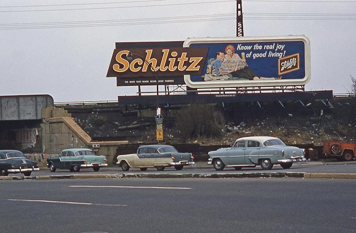 A Schlitz billboard sign above a highway in the 70s