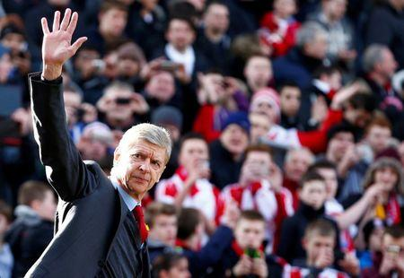 FILE PHOTO: Arsenal manager Arsene Wenger waves as he walks onto the pitch before their English Premier League soccer match against Stoke City at Britannia stadium in Stoke-on-Trent, central England March 1, 2014. REUTERS/Darren Staples//File Photo