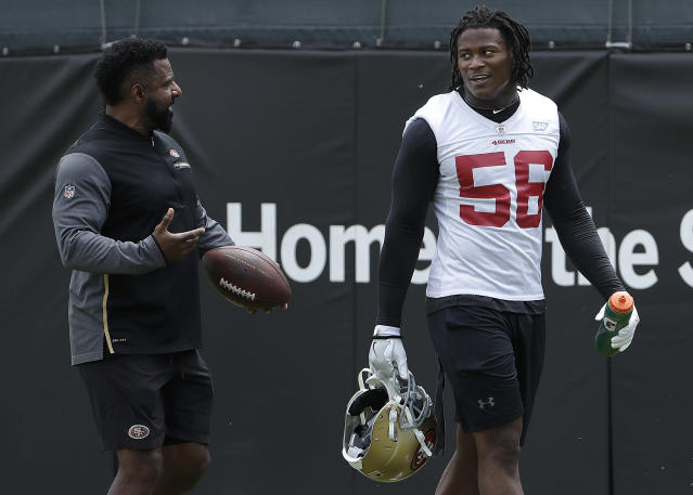 FILE - In this May 30, 2018, file photo, San Francisco 49ers linebacker Reuben Foster (56) walks on the field with assistant coach Ray Wright during a practice at the team's NFL football training facility in Santa Clara, Calif. 49ers linebacker Reuben Foster has been suspended without pay for the first two games of the regular season for violating the NFL's conduct and substance abuse policy. The NFL said Tuesday, July 3, 2018, that Foster will also be fined for violations from a weapons offense and misdemeanor drug charge that were resolved earlier this offseason.(AP Photo/Jeff Chiu, File)