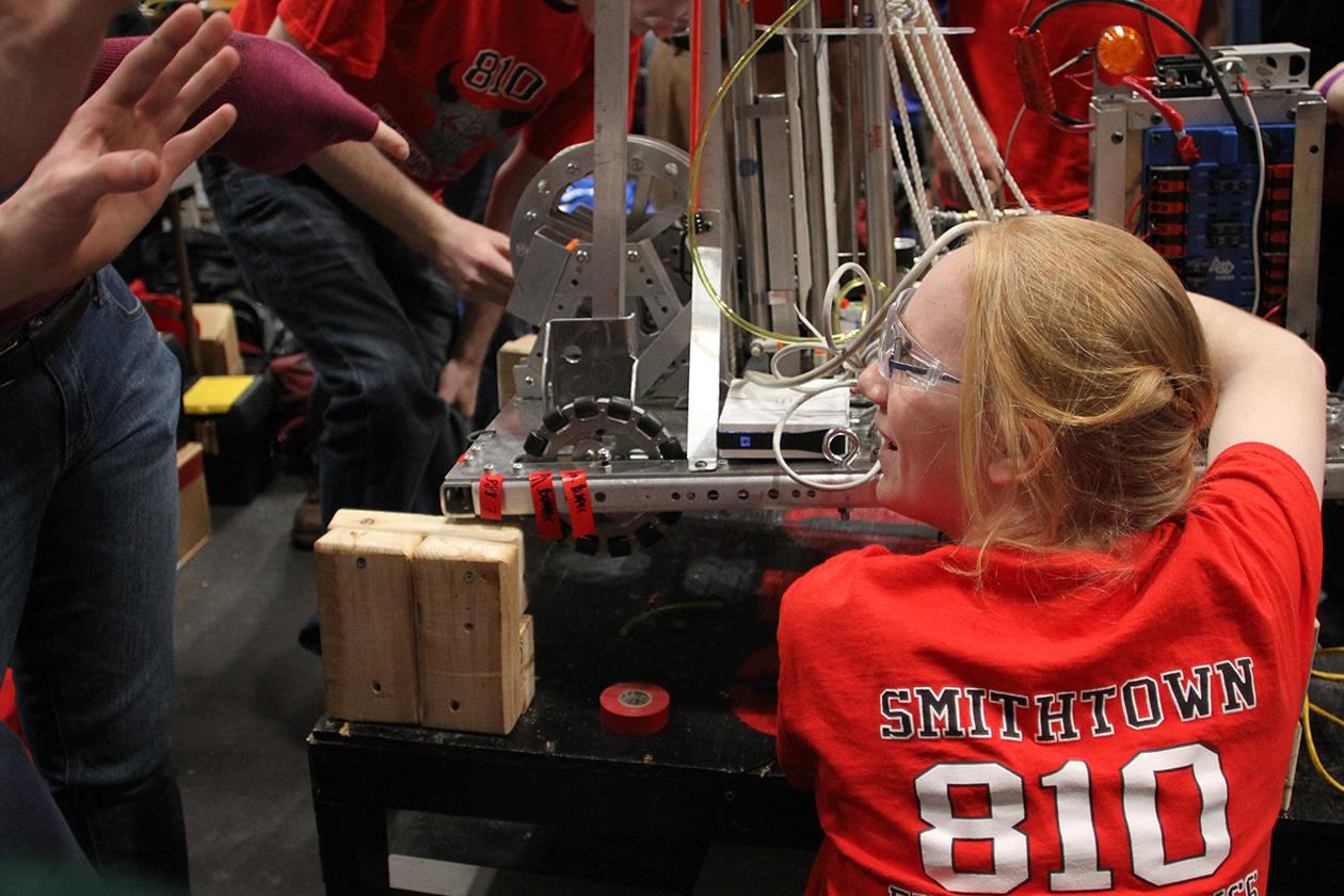 A member of the Smithtown robotics team is making some last minute adjustment to a gearbox while listening to her coach's advice for their next match.