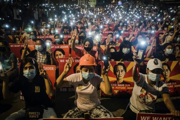 Protesters hold up the three-finger salute and images of Aung San Suu Kyi during a demonstration against the military coup in Yangon