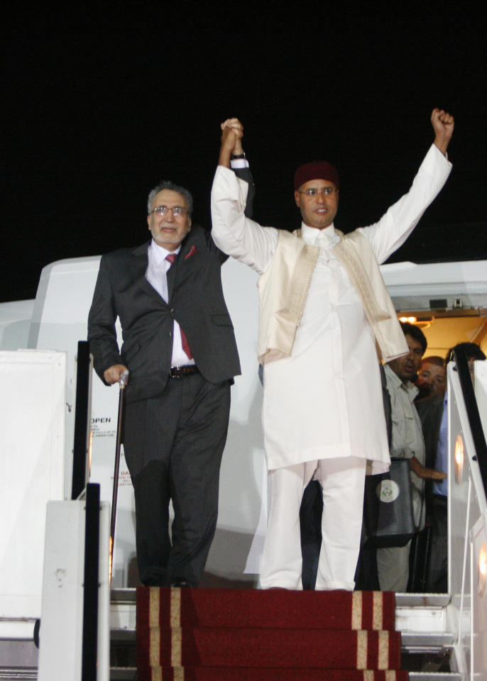 "FILE - In this Thursday, Aug. 20, 2009 file photo, Libyan Abdel Baset al-Megrahi, left, who was found guilty of the 1988 Lockerbie bombing, and son of the Libyan leader Seif al-Islam Gadhafi, gesture on his arrival at an airport in Tripoli, Libya following his release from a Scottish prison. The former Labour government did ""all it could"" to help Libya secure the release of the Lockerbie bomber Abdel Baset al-Megrahi, Britain's top civil servant Sir Gus O'Donnell said Monday Feb. 7, 2011. (AP Photo, File)"