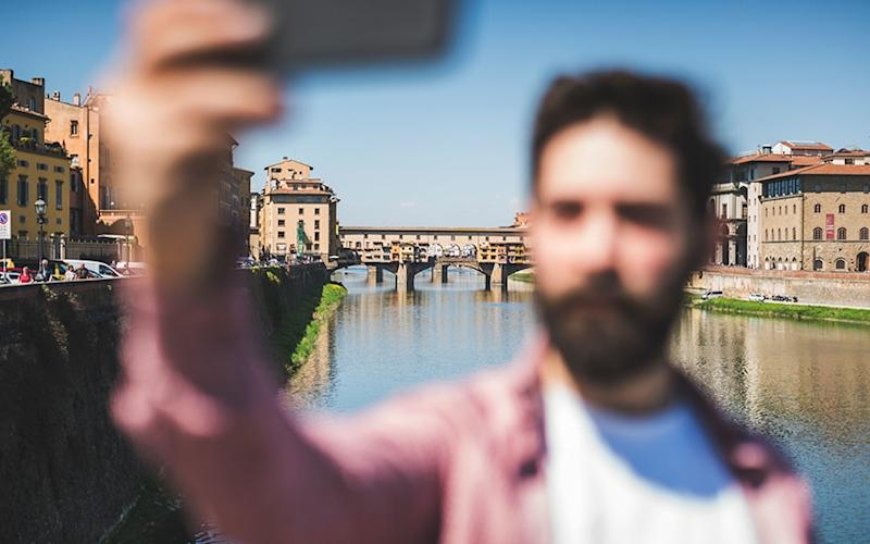 A selfie-taker in front of the original museum of selfies, the Vasari corridor, which runs above the Ponte Vecchio - This content is subject to copyright.