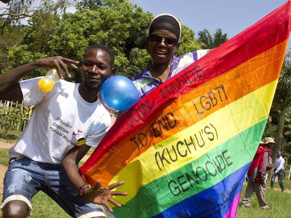 Ugandan men hold a rainbow flag reading 'Join hands to end LGBTI (called Kuchu in Uganda) genocide': ISAAC KASAMANI/AFP/Getty Images
