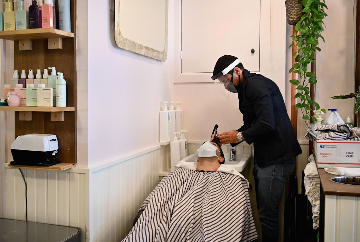 Benoit Peyrouse wears PPE (personal protective equipment) as he washes a client hair at 'Les Enfants Terribles' hair salon and barber shop on June 22, 2020 in Brooklyn.
