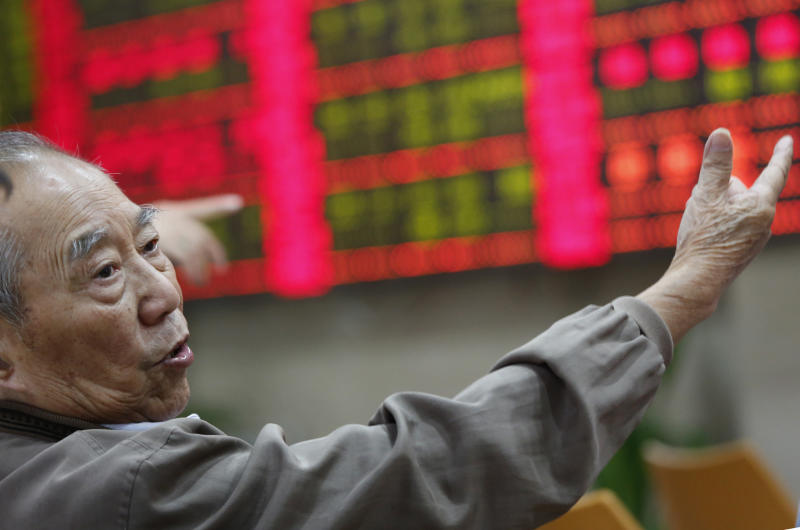 An investor gestures at a private securities company in Shanghai, China Wednesday, Oct. 23, 2013. Asian stock markets mostly fell Wednesday, hit by slower U.S. hiring and reports of tighter money market conditions in China that could check its economic recovery. (AP Photo)