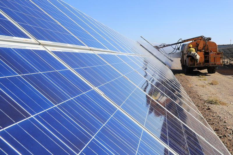 Worker operates a machinery to clean solar panels at a photovoltaic industrial park in Hami