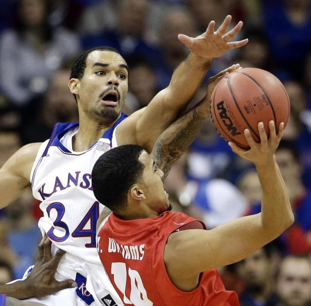 Kansas' Perry Ellis (34) tries to block a shot by New Mexico's Kendall Williams during the first half of an NCAA college basketball game Saturday, Dec. 14, 2013, in Kansas City, Mo. (AP Photo/Charlie Riedel)