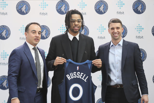 New Minnesota Timberwolves NBA basketball player D'Angelo Russell, center, holds his new jersey between President of Basketball Operations Gersson Rosas, left, and head coach Ryan Saunders during his introduction to the media, Friday, Feb. 7, 2020, in Minneapolis, following a trade that sent Timberwolves' Andrew Wiggins to the Golden State Warriors. (AP Photo/Jim Mone)