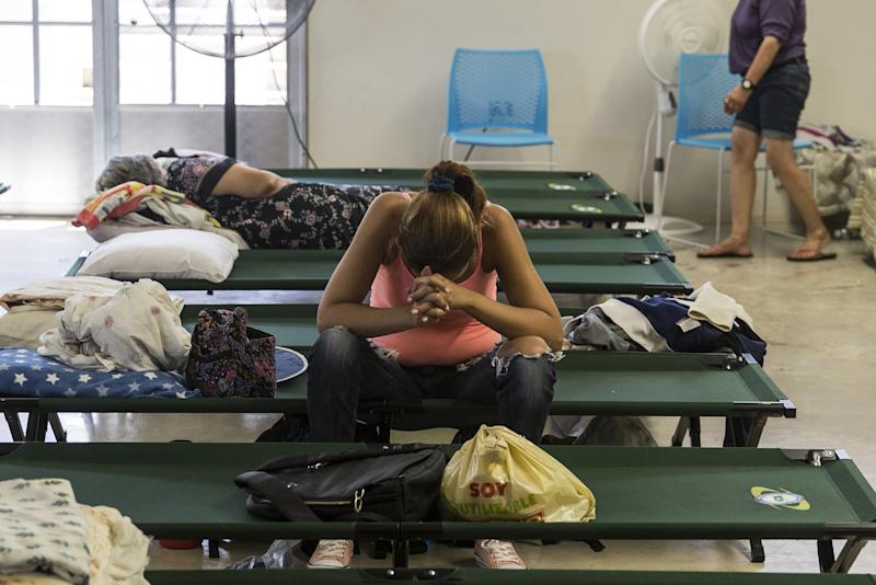 A resident sits inside a shelter in Isabela, Puerto Rico, after being evacuated from her home in the wake ofHurricane Maria. (Bloomberg via Getty Images)