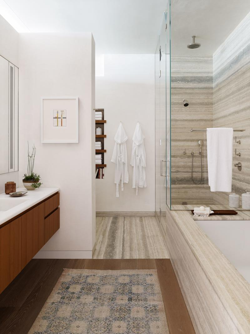 The master bath is a study in stone. Santos carefully chose travertine with a blue hue that flows perfectly to create a water-like effect.